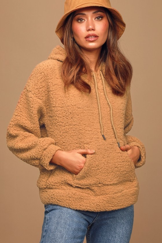model wearing a tan sherpa sleeved hoodie with drawstring and front pocket