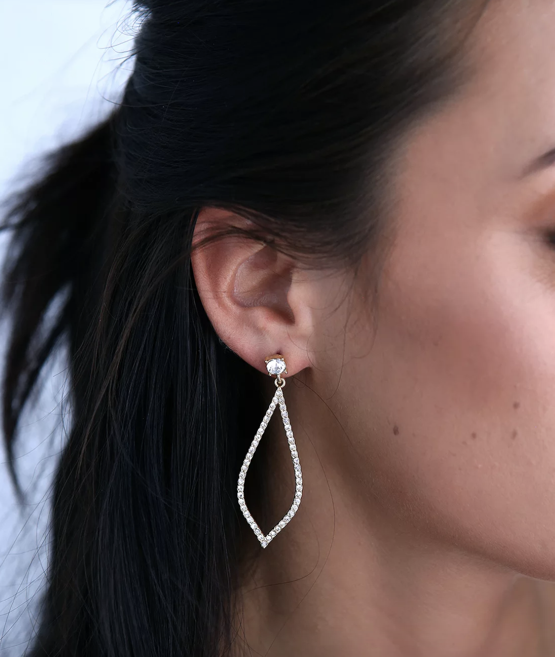 model wearing teardrop-shaped earrings with rhinestones