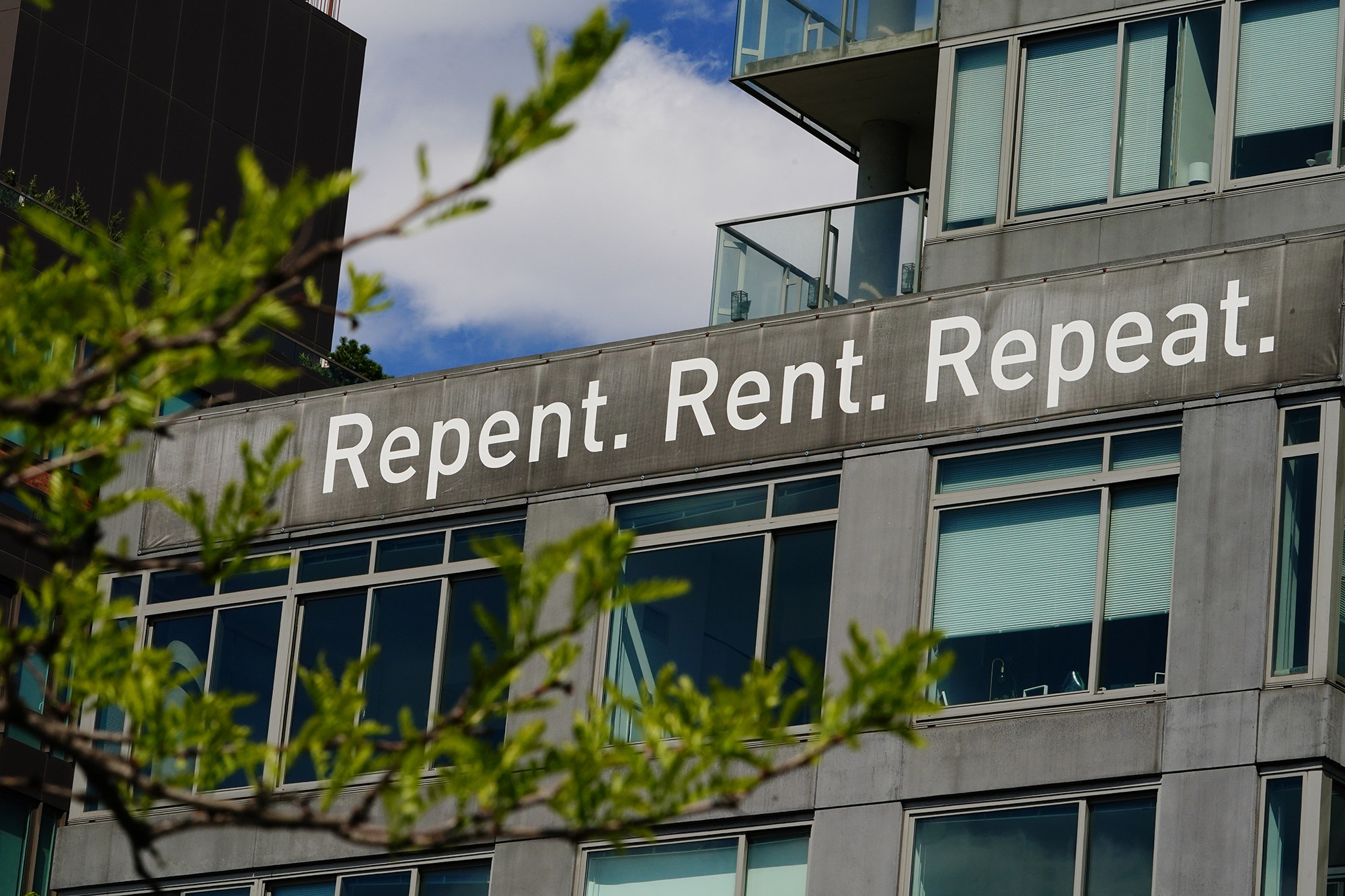 "A view of a sign in New York City reading ""Repent. Rent. Repeat."""