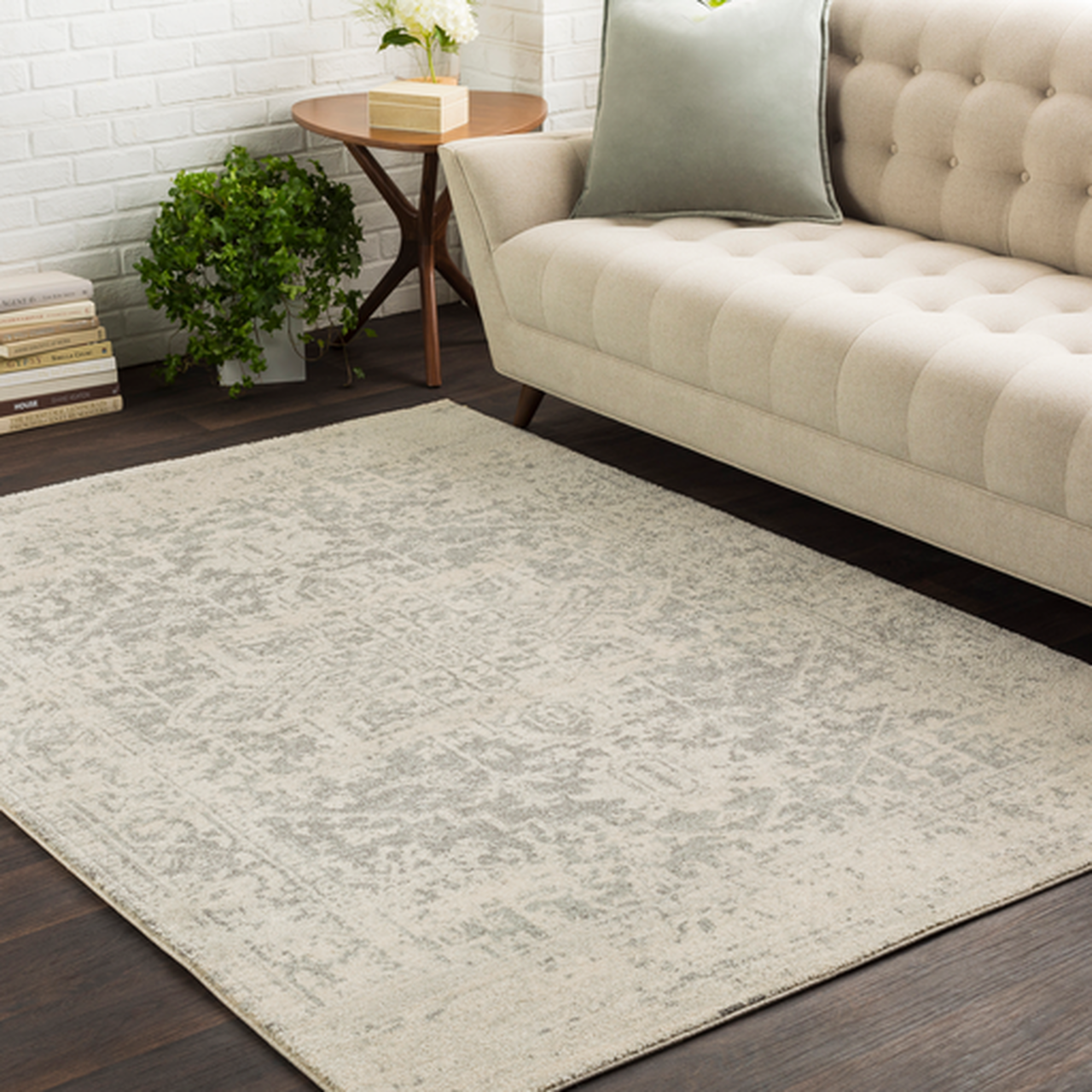 A neutral-color rug on a hardwood floor in front of a matching couch
