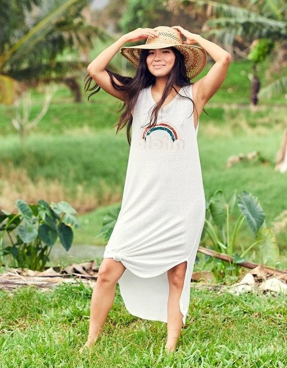 A model wearing the white midi dress with a rainbow design and the word aloha both on the chest. The dress has been styled with a knot at the knee.