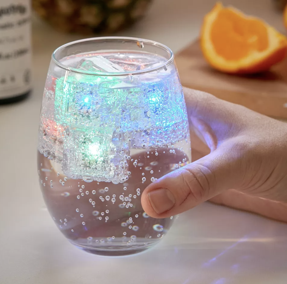 A person holding a transparent glass full of fizzy seltzer with multicolored glowing ice cubes floating at the top