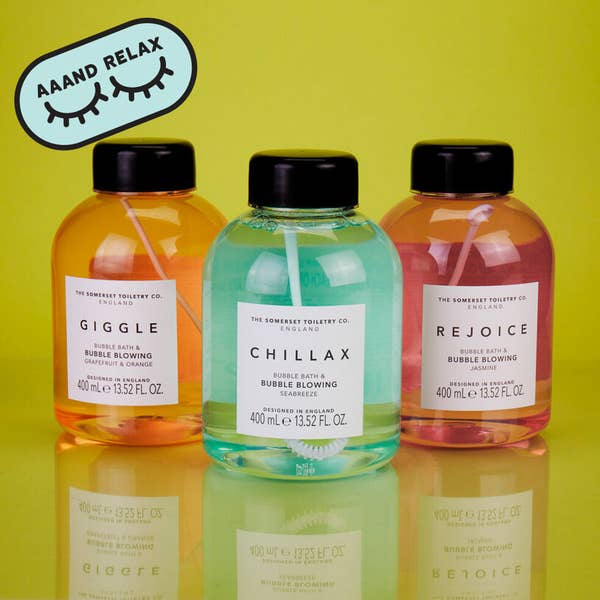 Three bottles of bubble bath with bubble blowing sticks inside of them, called Giggle, Chillax, and Rejoice