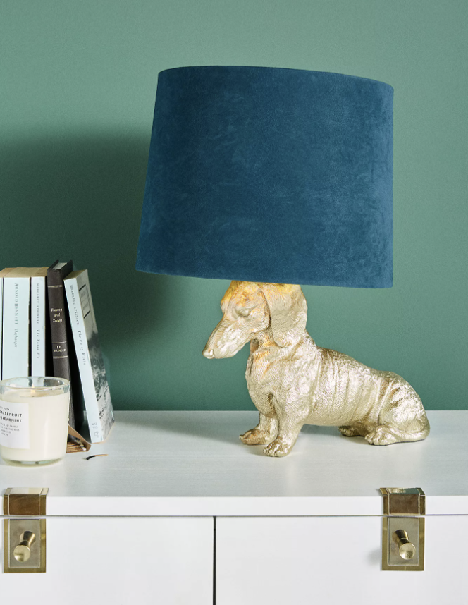 A lamp that has a golden dachshund as the base and velvet blue lampshade sitting on top of a dresser