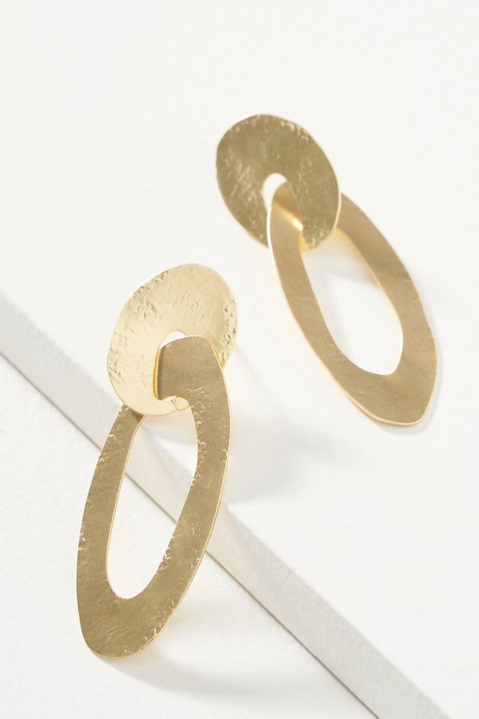 A pair of golden disc earrings, each made of two intertwining pieces, displayed on a white background