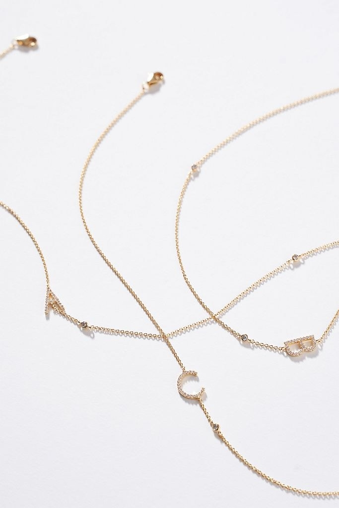 Three separate intertwining gold necklaces with the letters A, B, and C on a white background
