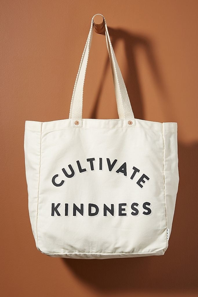"A cotton tote bag that says ""Cultivate Kindness"" hanging from a wooden hook on a brown wall"