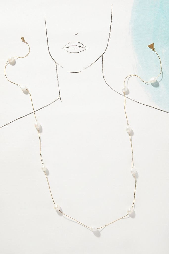 A gold necklace with white pearls spread out around it, laying on top of a sketch of a person's face