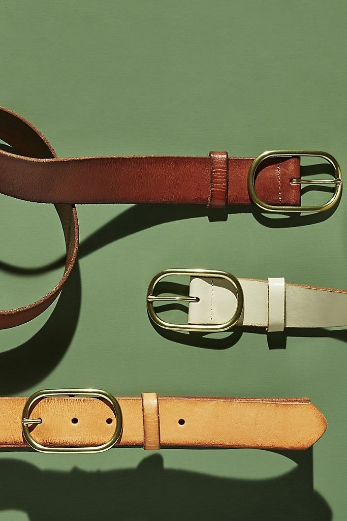 Three leather belts with gold, oval buckles over a solid green background