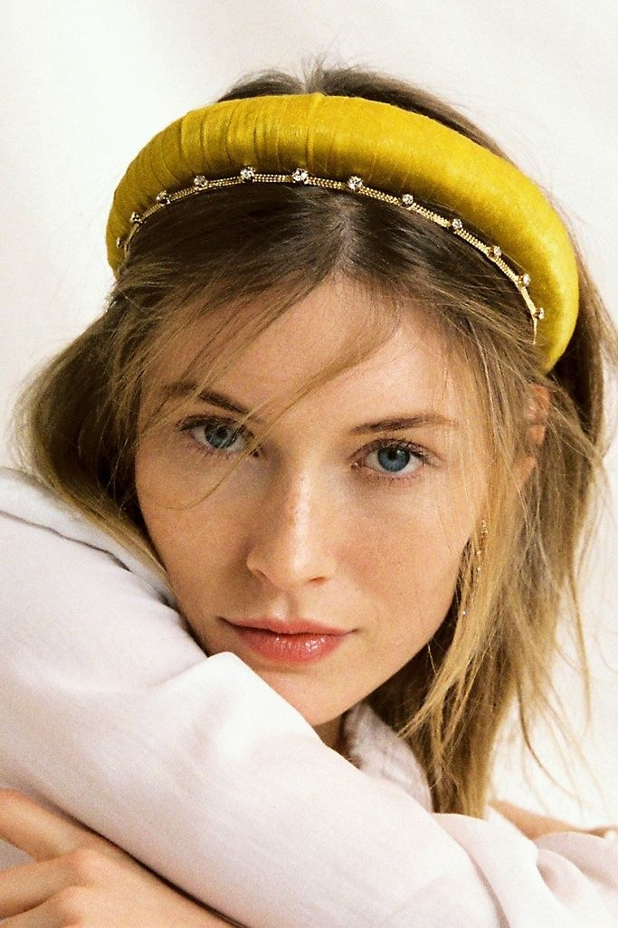 A model wearing a large gold satin headband, accessorizing with a smaller diamond headband and hair down