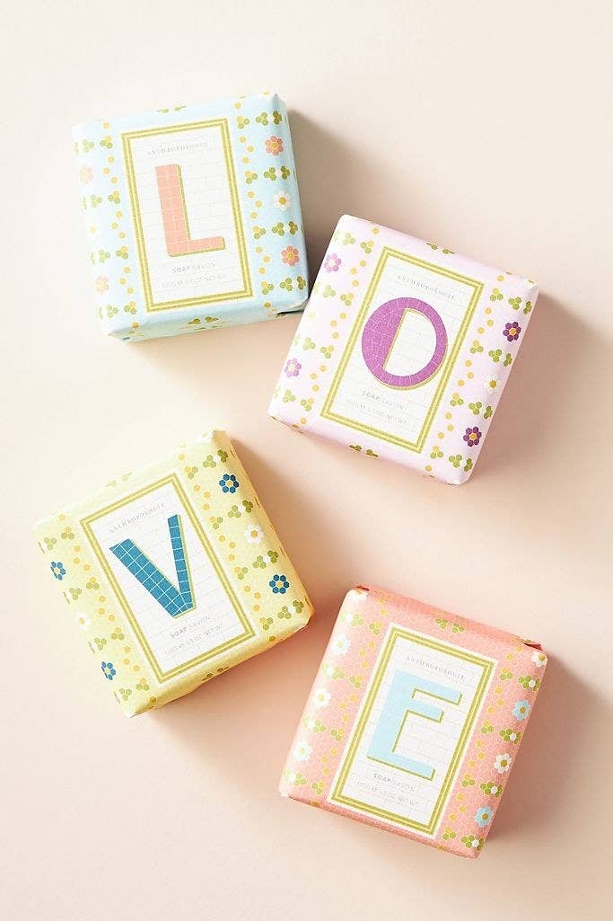 A set of four bar soaps wrapped in packaging that spells out the word love