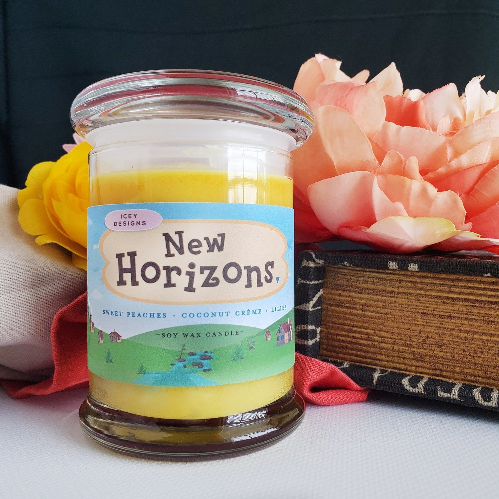 """A glass candle with a glass lid with a sticker around it that says """"New Horizons"""" with the Animal Crossing logo, and describes the small as sweet peaches, coconut creme, and lilies."""