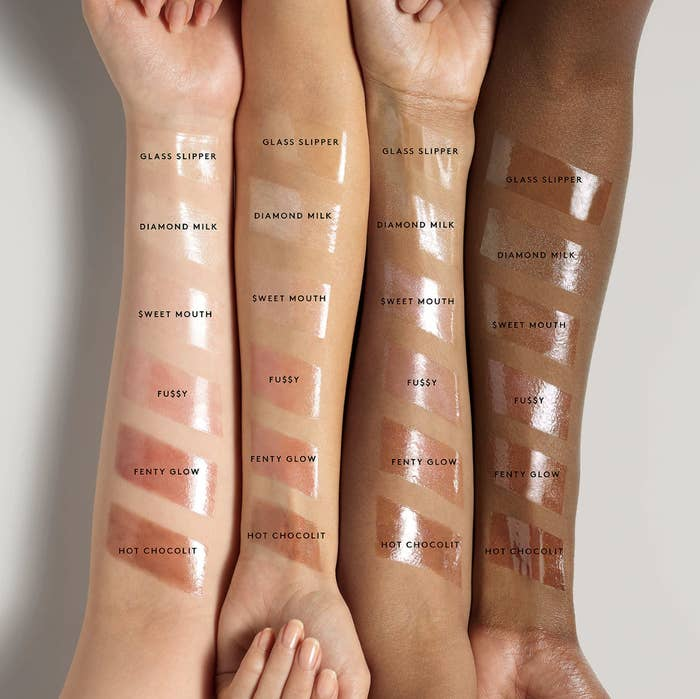 Six Fenty Gloss Bomb swatches on the arms of people with light, medium, tan, and deep skin tones