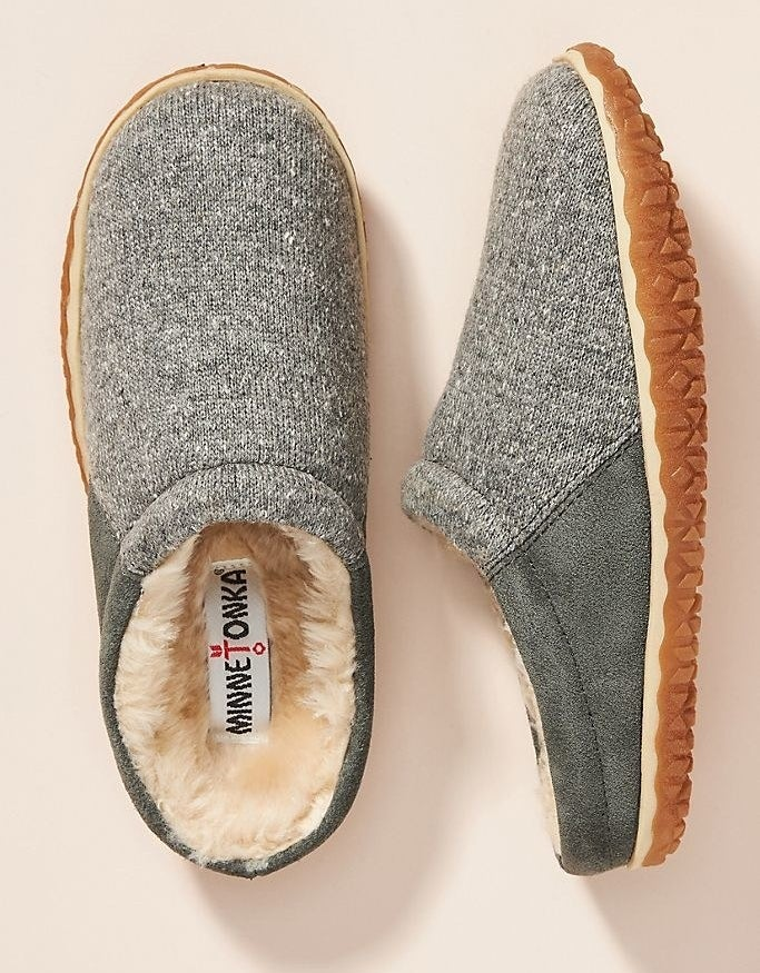 A pair of gray slippers with fuzzy interior, one laying on its side