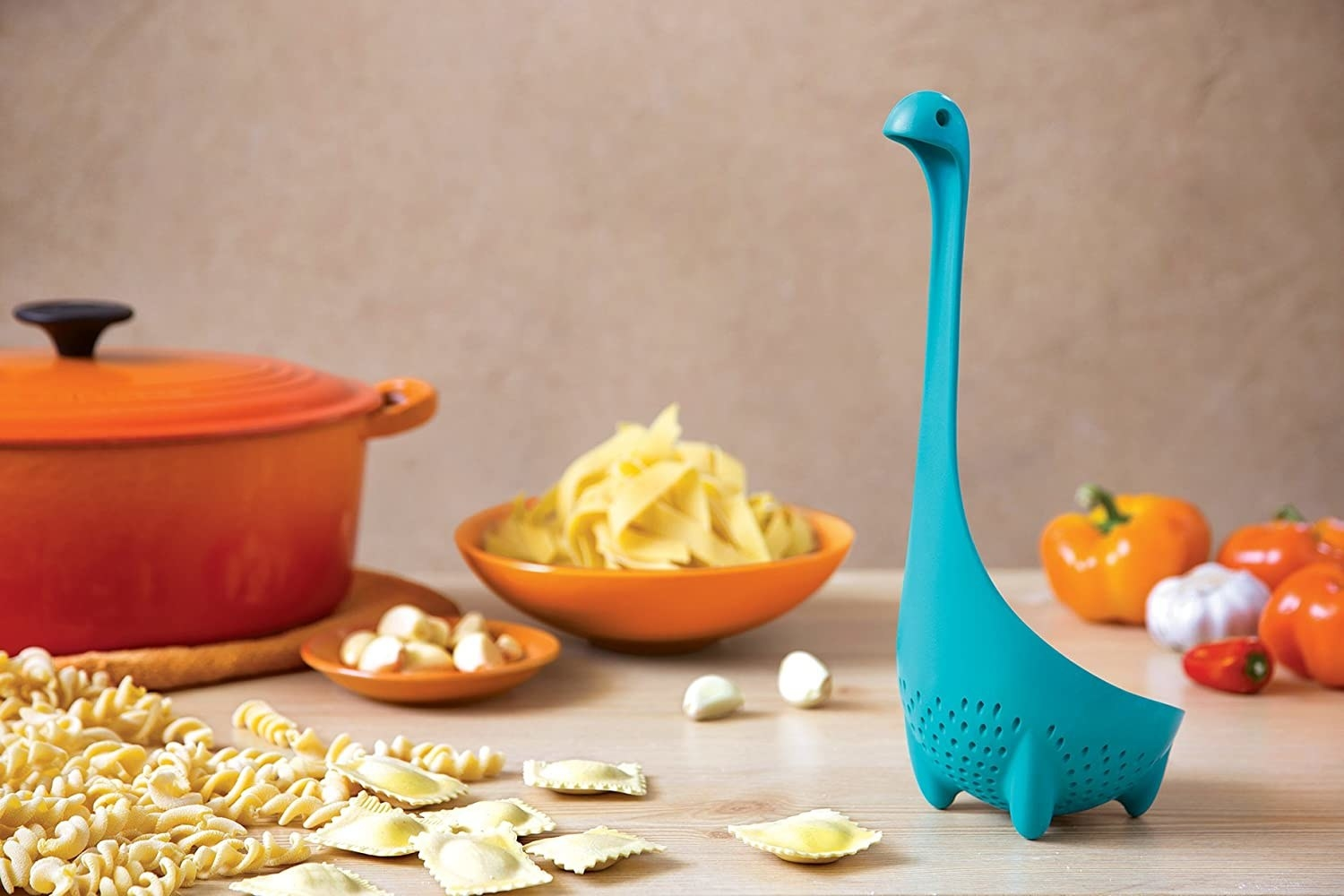 A blue ladle with a long neck and a little head shaped like the Loch Ness monster perched on a table.