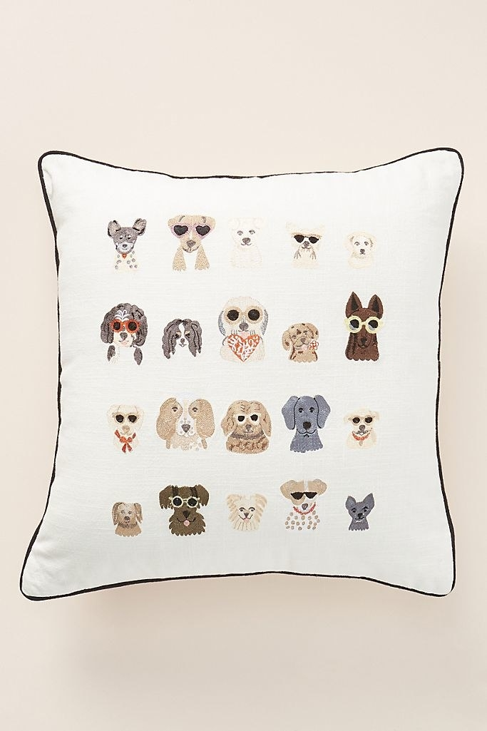 a cream colored throw pillow with 20 embroidered dogs on it (some are wearing sunglasses)