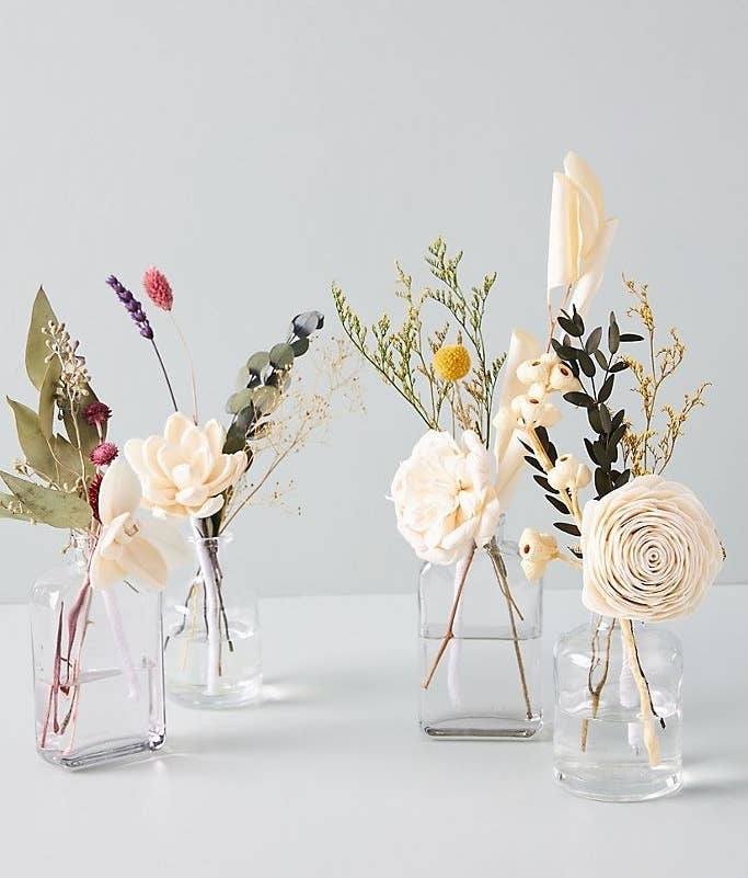 A display of four faux floral diffusers placed in clear jars filled with water