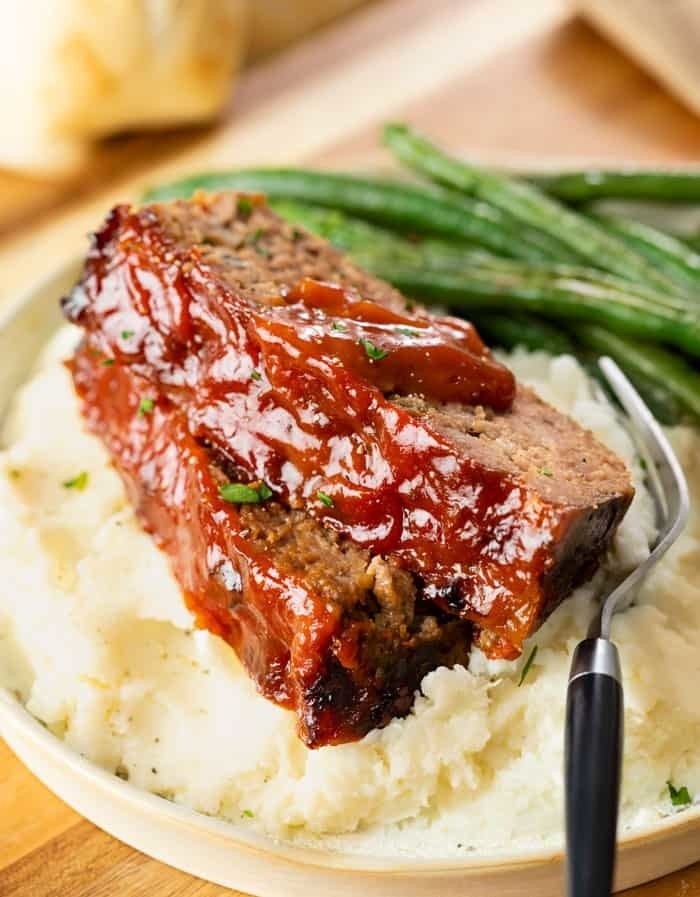 Two slices of meatloaf with ketchup glaze on a bed of mashed potatoes.