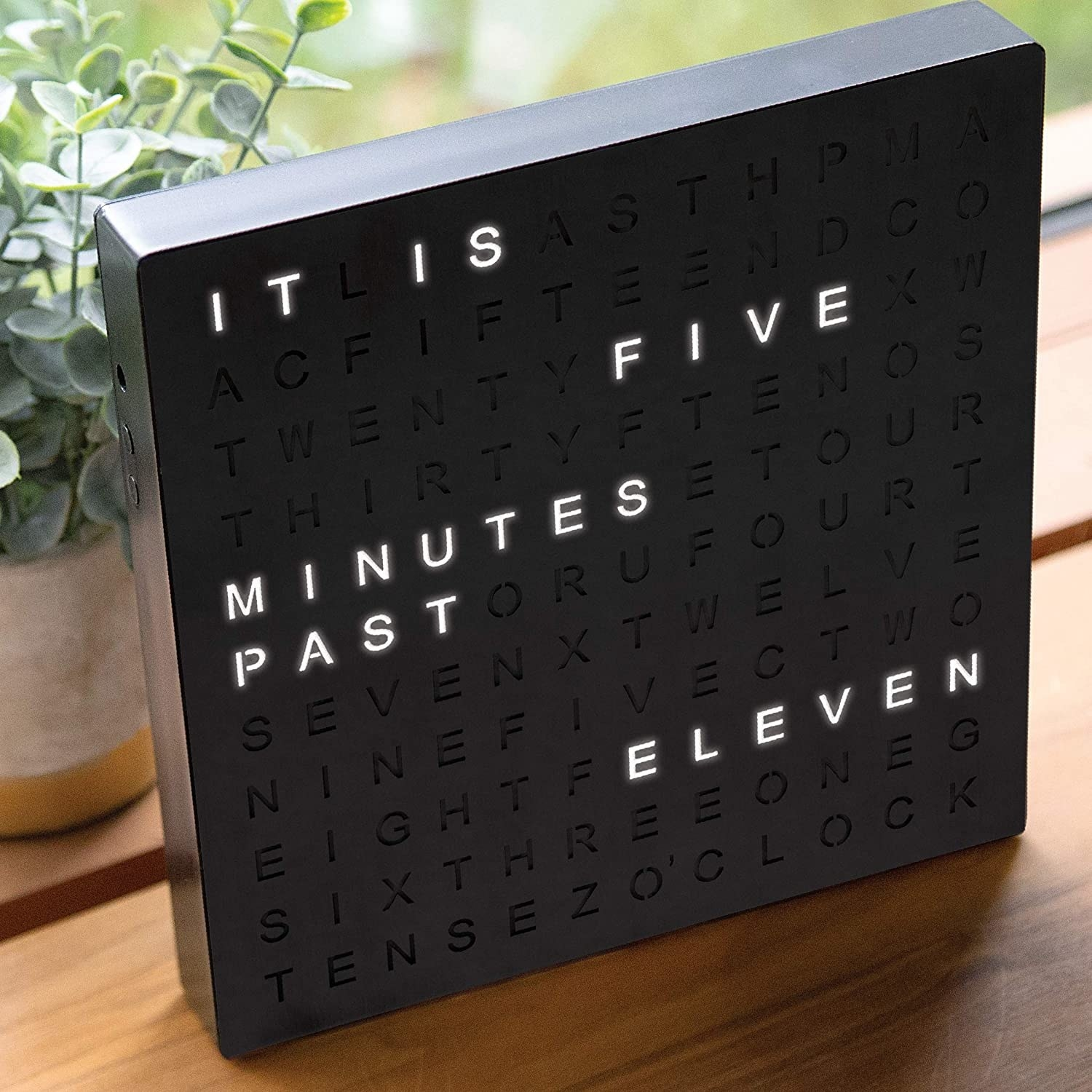 The black digital clock with light-up letters spelling out the time. The display reads it is five minutes past eleven