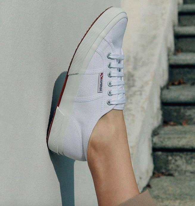 person placing their foot with a white Superga 2750 Cotu sneaker on it up against an outdoor wall