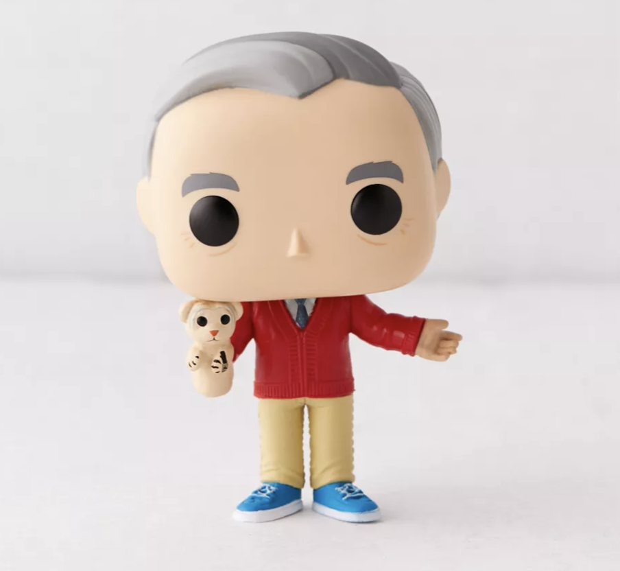 A cartoonish figure resembling Mister Rogers about six inches tall holding his Daniel Tiger puppet