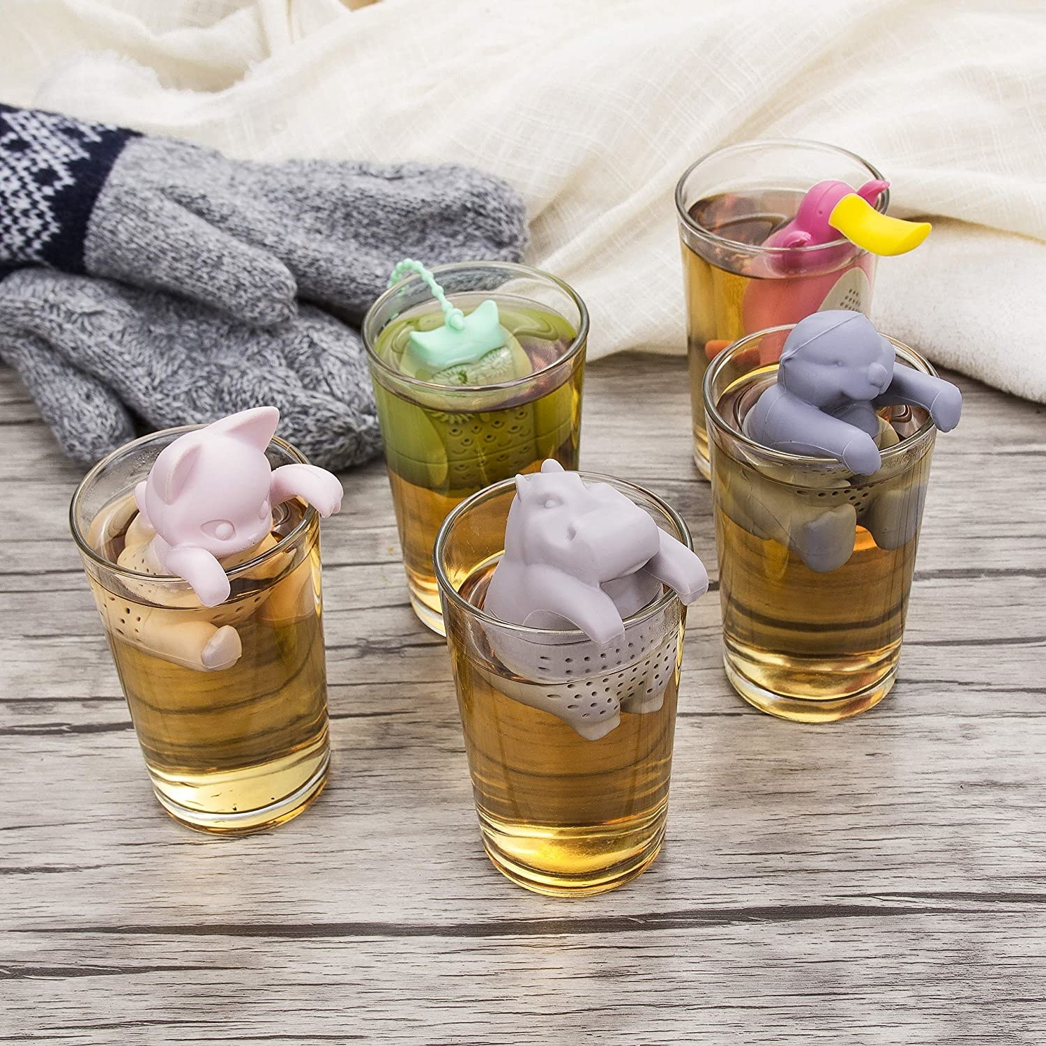 Five infusers shaped like a cat, a hippo, a sloth, an owl, and a platypus in clear tea glasses.