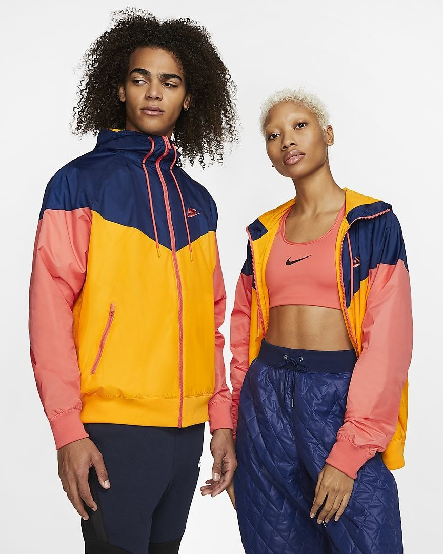 Two models facing front wearing the same pink, blue, and orange hooded windbreaker, one is zipped up, the other is unzipped