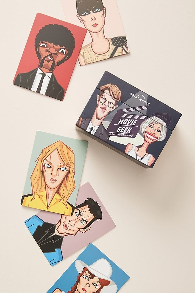 "An illustrated movie trivia box with the game title ""Movie Geek"" laying on a beige background with loose cards outside of it, each featuring a stylized version of famous characters in hit movies"
