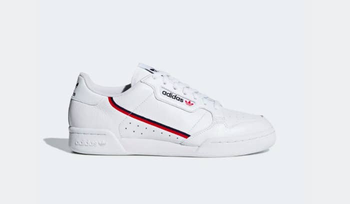 White shoe with one thin black stripe and one thin red stripe going down the outside of the shoe parallel to the laces