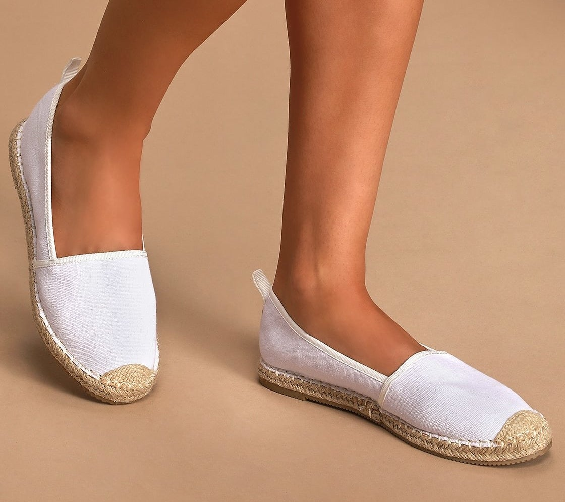 Closeup of model wearing white slip-on espadrilles made with canvas fabric and a rounded toe upper