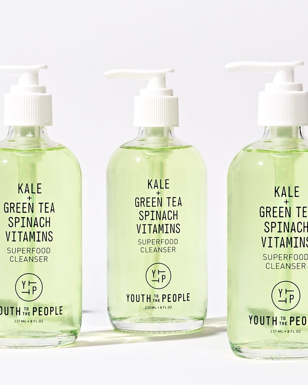 Three bottles filled with the light green cleanser — the bottles have a pump top