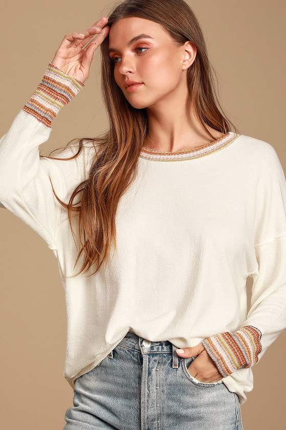 Model wearing pullover sweater with a scoop neckline, drop shoulders, and red, orange, and blue striped knit trims on the neckline and sleeve cuffs