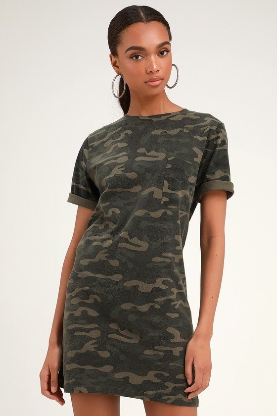 Model wearing green camo print t-shirt dress with rolled and cuffed sleeves