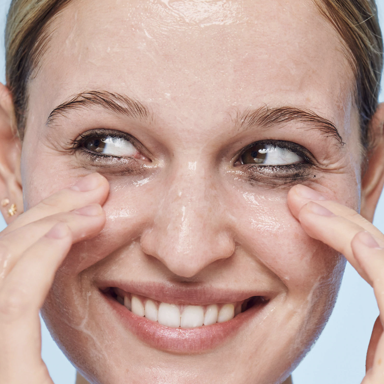 A person with the clear wash spread across their nose, forehead, and cheeks. The product is helping to remove the eyeliner from around the person's eye area