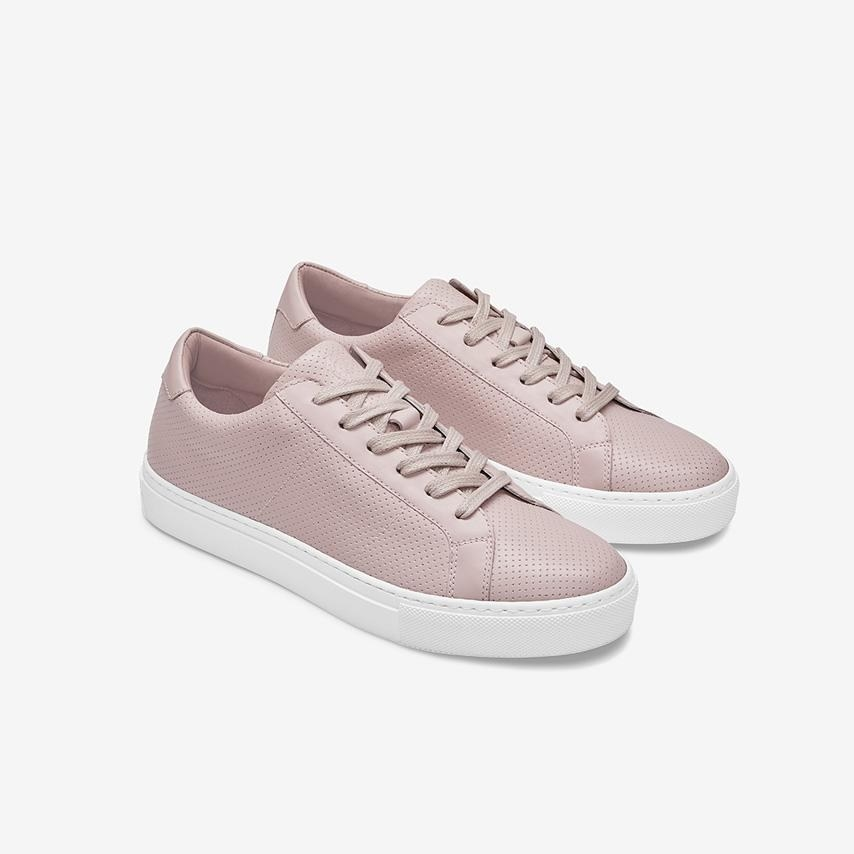 A pair of pink perforated sneakers with a thick white sole