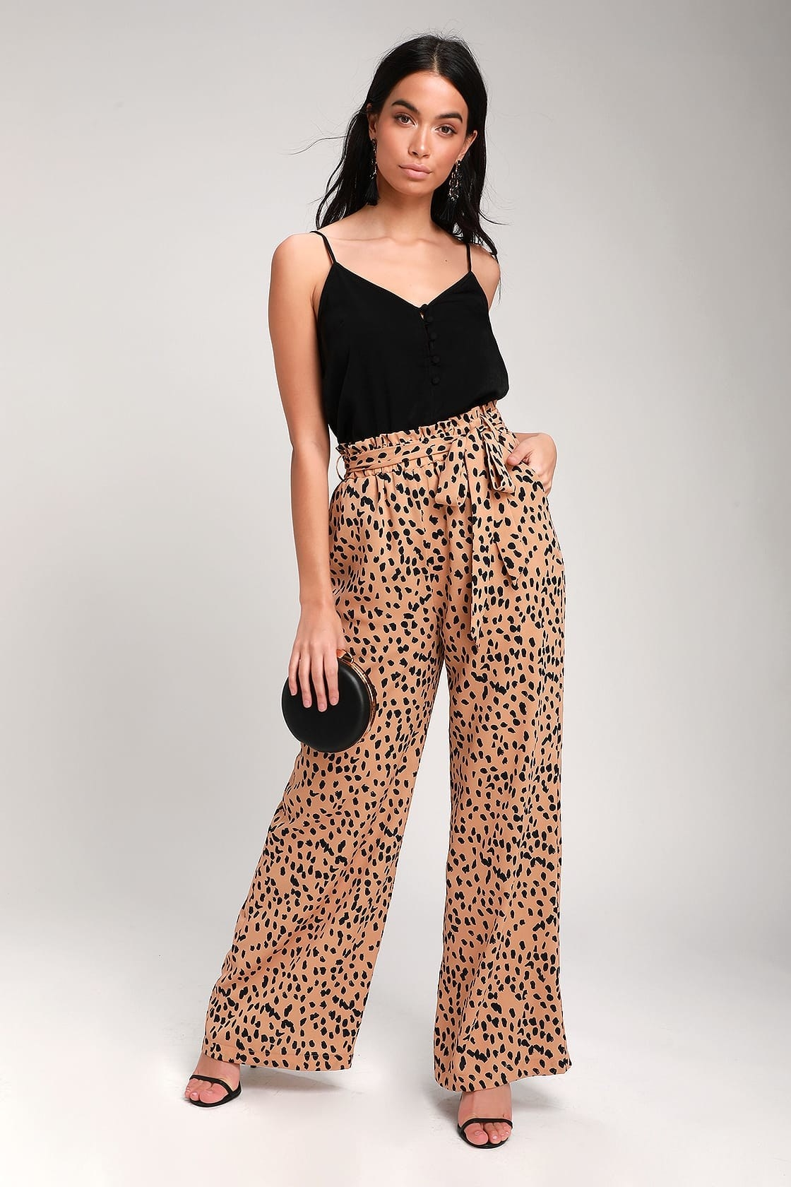 Model wearing wide-leg leopard print pants with a paper-bag waist, tie sash, and pockets