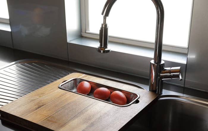 Tomatoes sitting in cutting board and strainer hybrid product.