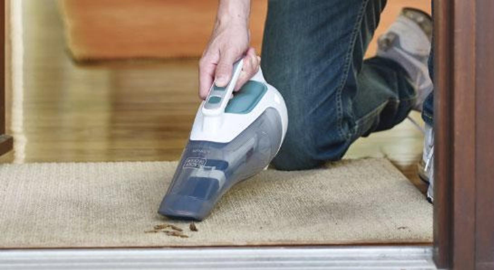 Una persona usa una aspiradora para limpiar un tapete