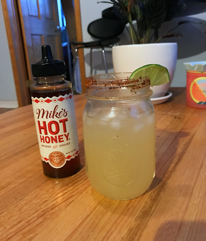 Someone on the BuzzFeed Shopping team using the hot honey to make spicy margaritas