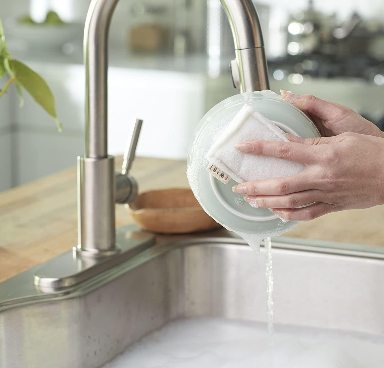 Una persona lava un plato con una esponja biodegradable