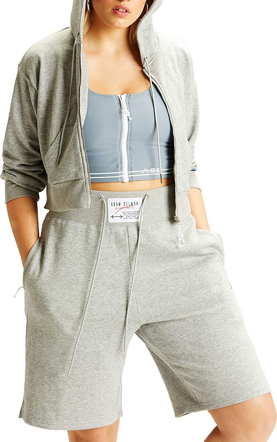 A model with her hands in her pockets wears the Adam Selman Sport hi-rise sweatshorts with a cropped hoodie and sports bra.