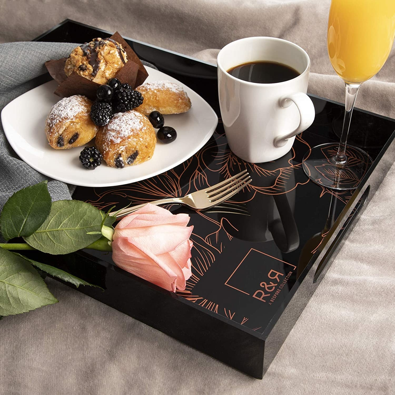The black floral acrylic tray on a bed with an elegant breakfast spread