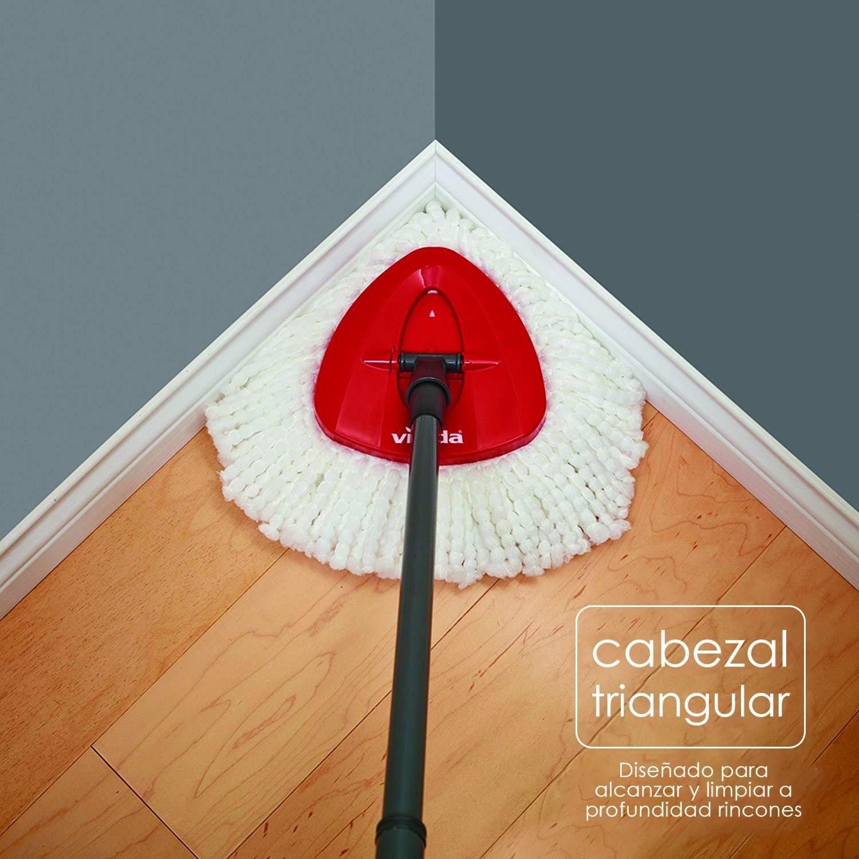 Mopeador con cabeza de microfibra limpia la esquina de una casa