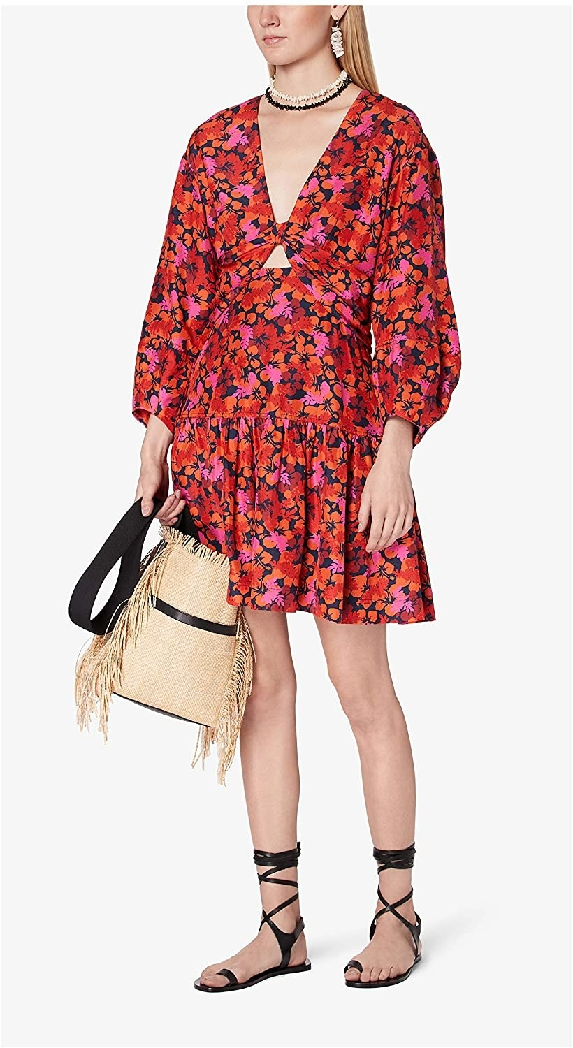 A model standing against a white background wearing the Derek Lam 10 Crosby Talia Dress in the midnight print while holding a woven straw tote and lace-up black sandals.