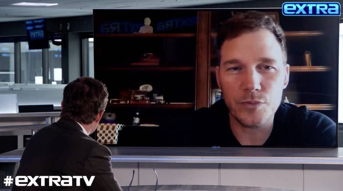 Chris appears on screen during in an interview with Extra TV.