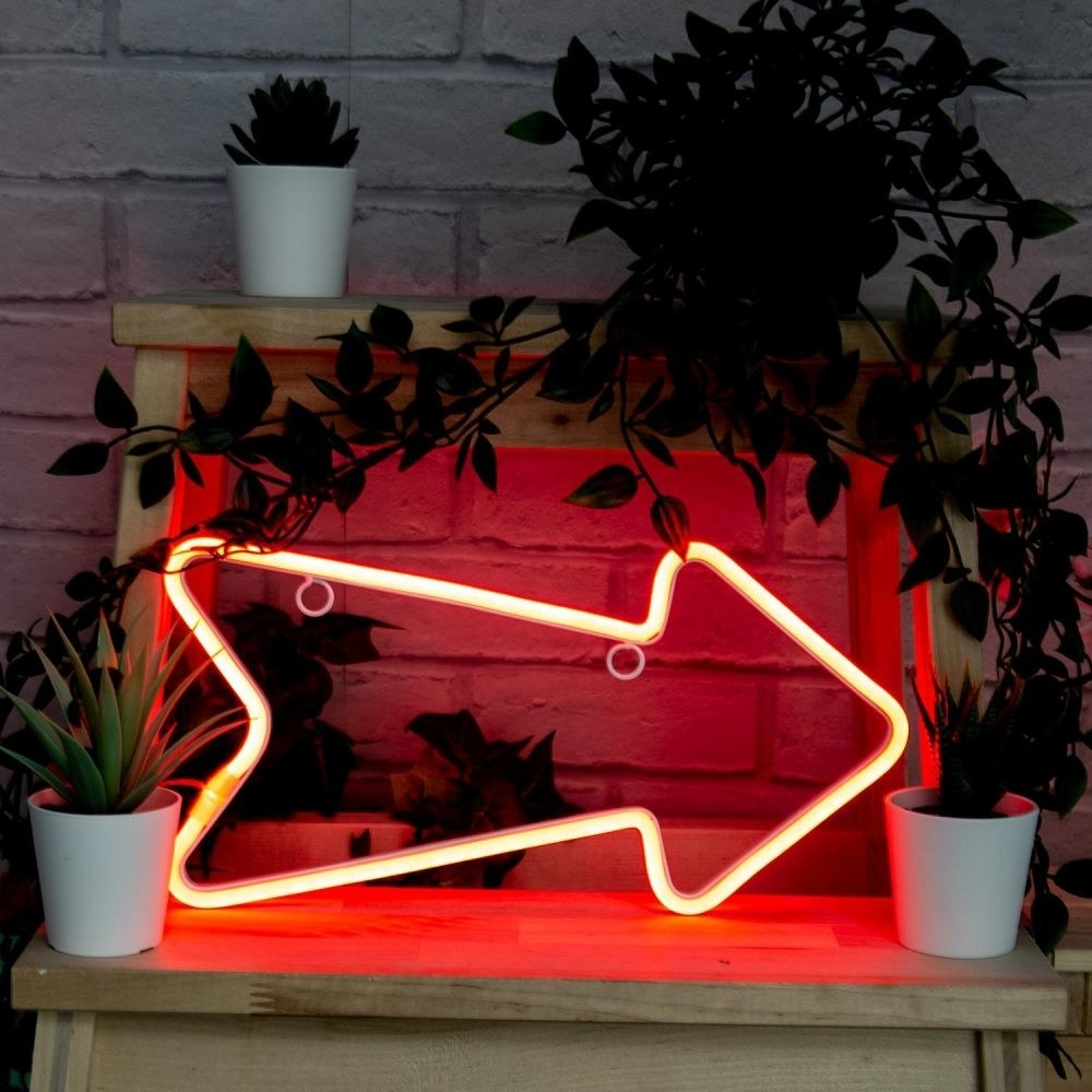Red neon arrow-shaped light on a bench