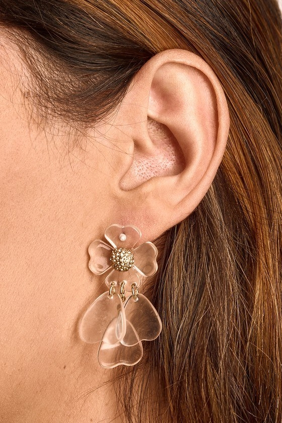 Closeup of lucite flower earrings with gold flower center and three heart-shape petals coming off the bottom of the flower post