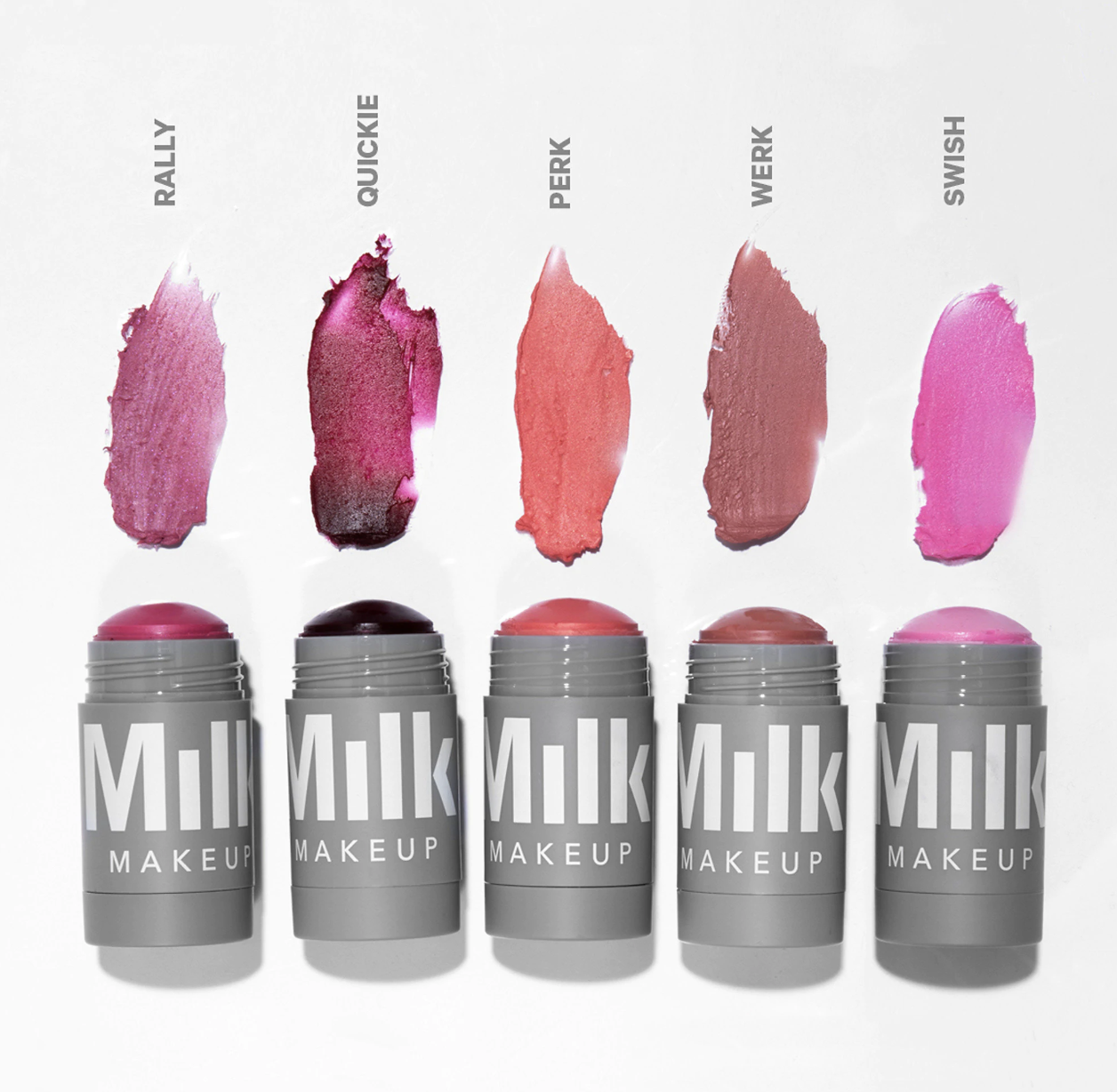 Five small tubes of the tint lined up next to each other with swatches above them. The shades include a light plum, deep cranberry, a pink peach, a brownish mauve, and a brighter pink color