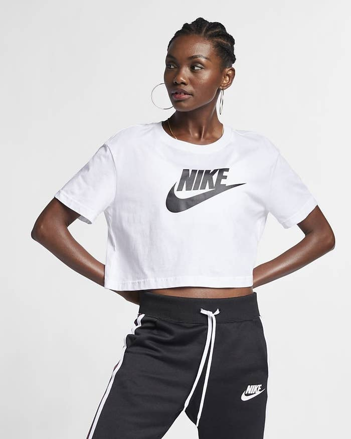 A model wearing a white cropped T-shirt with a black Nike Swoosh logo as well as black Nike track pants