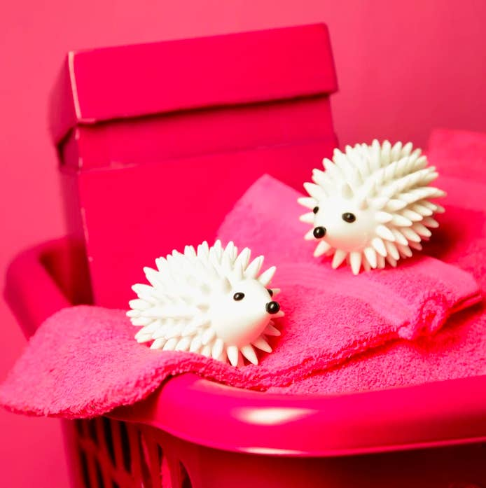 Two hedgehog dryer balls in a laundry basket